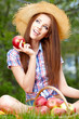 Smiling Young Woman Eating Organic Apple in the Orchard.Basket o