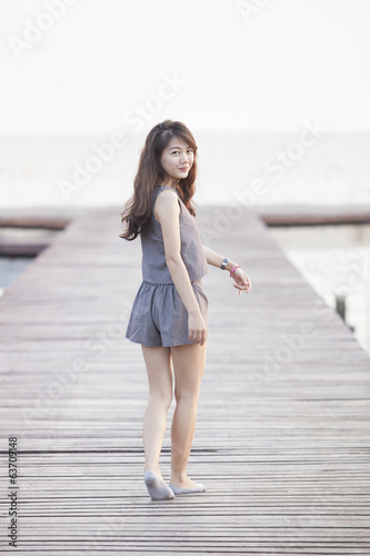 beautiful woman walking on wood pier with relaxing emotion