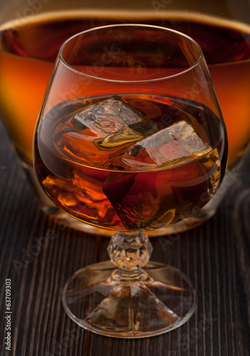 Whiskey with ice on dark wooden background