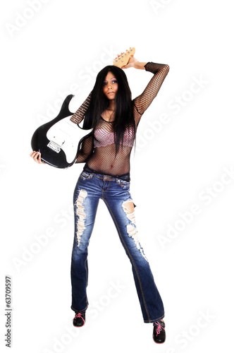 Girl standing with guitar.