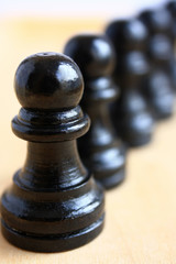 Pawn chess pieces on a brown background macro.
