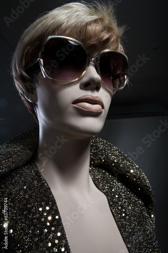 Female mannequin in a dress, wig and glasses