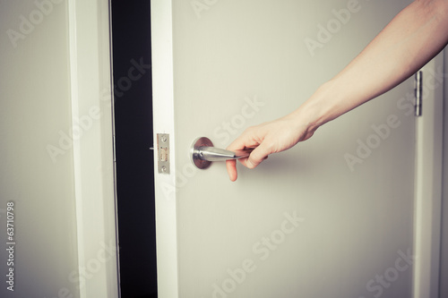 Woman opening a door at night