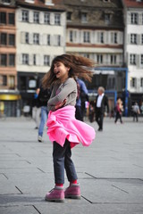 Girl spins around herself in the square