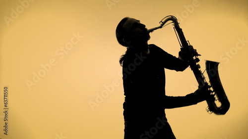 Young man playing sax in the dark