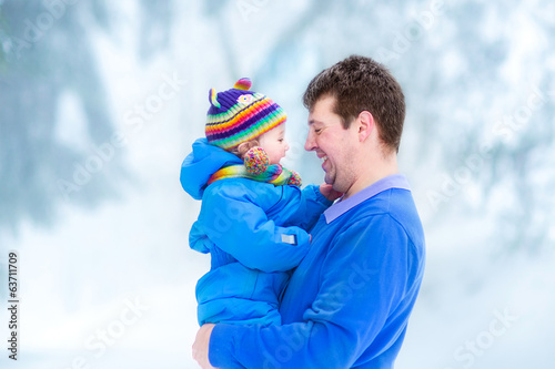 Young father playing with his funny baby in a snowy park