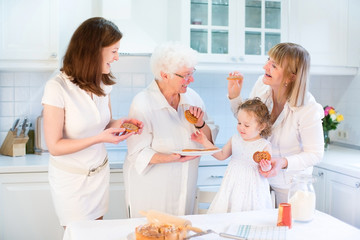 Four generations of women having fun together baking apple pie