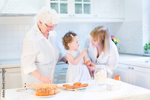 Happy funny toddler girl playing in a white beautiful kitchen