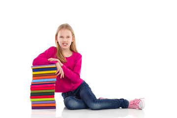Cute young girl leaning on a stack of books