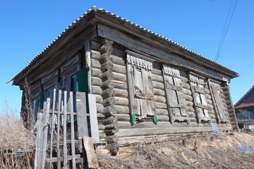 Deserted old log rural house against a blue sky