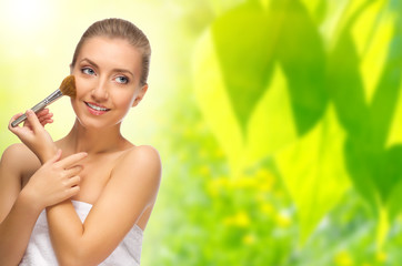 Healthy woman with makeup brush on spring background