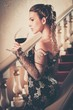 Woman in long evening dress with glass of red wine