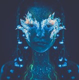 Woman with body art glowing in ultraviolet light poster