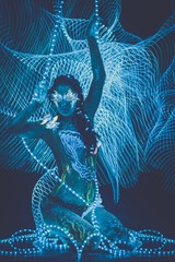 Woman with body art glowing in ultraviolet light