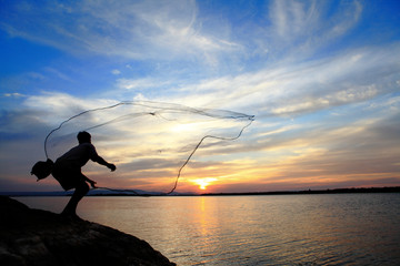 Fisherman casting his net at sunrise
