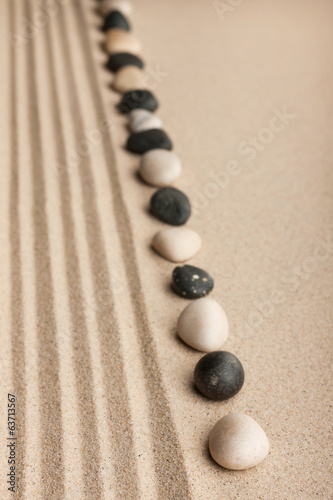 Stripe of white and black stones lying on the sand