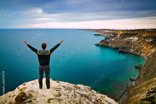 young man stands on a hill with raised hands