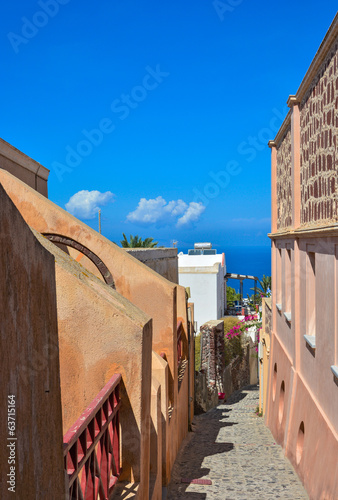 Narrow street in Oia, Santorini, sea view.