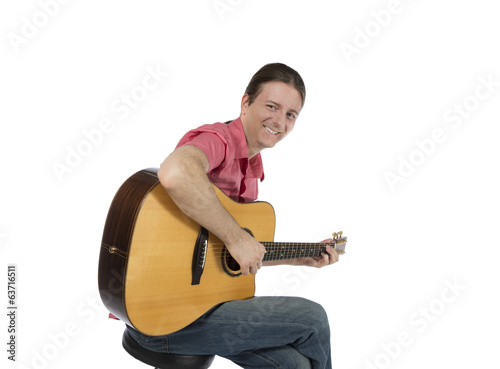 Guitar player playing his acoustic guitar with a smile
