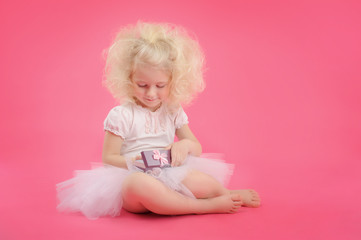 little girl in a skirt and a gift pack on a pink background