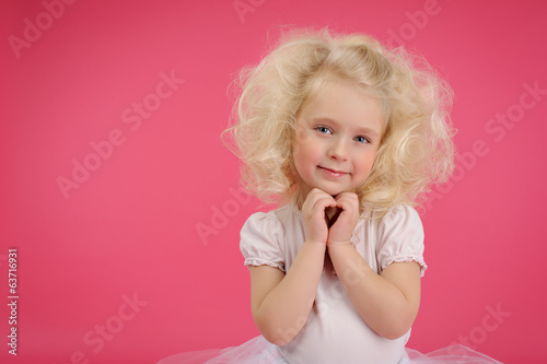 Little girl in a tutu skirt on pink background