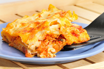 Piece of lasagna on a blue plate on a wooden salver.