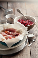 Raw pork in a bowl, cranberries, seasonings and meat hammer