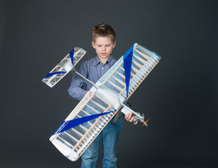 Teenager boy holding a wooden plane model