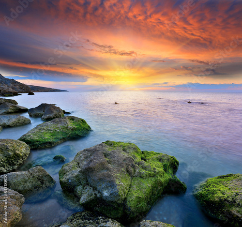 stones in sea water on sunset background