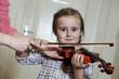 cute preschool girl learning violin playing