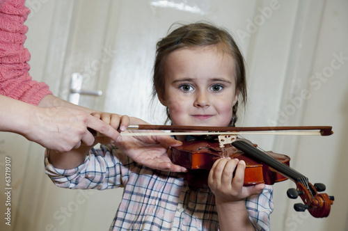 cute preschool girl learning violin playing