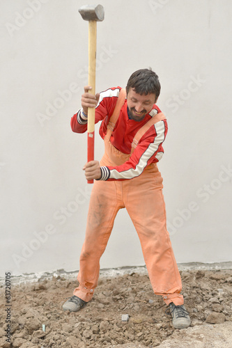 workman with sledge hammer