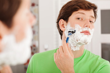 Man shaving in bathroom