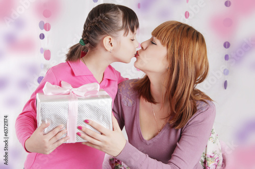Mother and daughter kissing and holding present