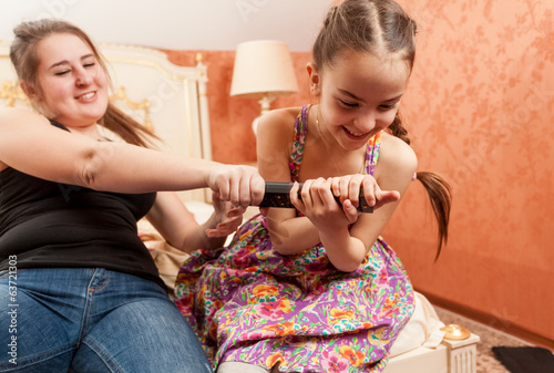 little girl pulling tv remote out of adult sister