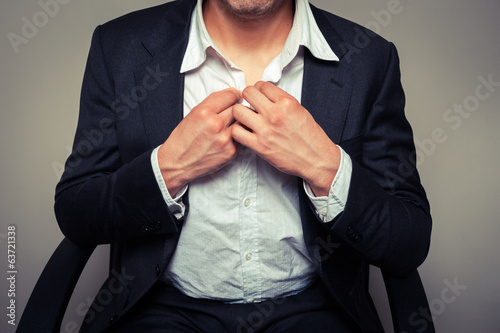 Businessman buttoning his shirt