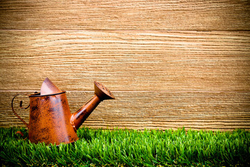 old and rusty watering can on green grass with wood background