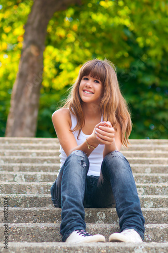 Pretty smiling teenage girl sitting on the stairs
