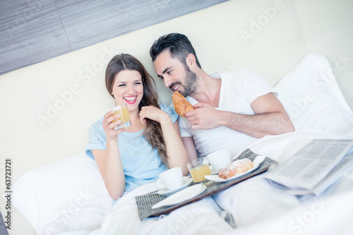 Happy man and woman having luxury hotel breakfast in bed togethe