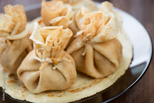 Glass plate with stuffed pancakes, horizontal shot, close-up