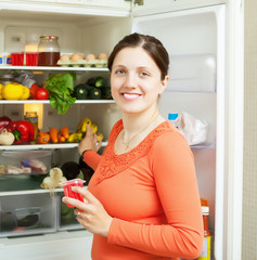 woman with fruits jam near fridge