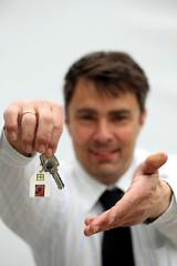 Makler hält freudig Schlüssel für Traumhaus hin