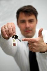 Makler zeigt auf Schlüssel, Hintergrund  freigestellt