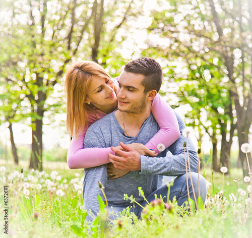 Happy couple embracing outdoor in park.