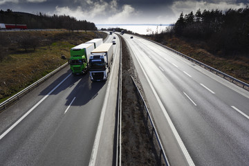two trucks on straight freeway, elevated view