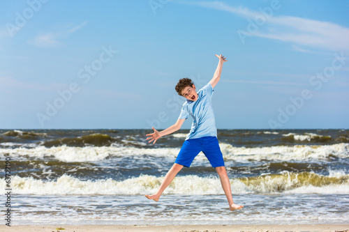 Teenage boy running, jumping on beach