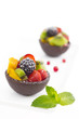 Fruit salad in chocolate cups on white background