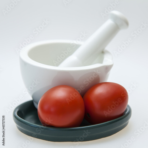 White porcelain mortar with pestle and tomatoes