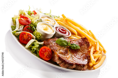 canvas print picture Grilled steak, French fries and vegetables
