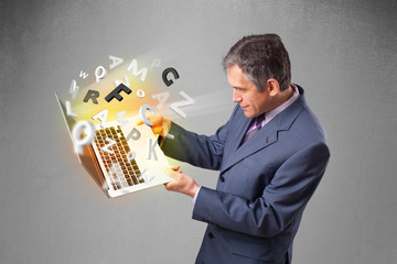 Middle aged businessman holding laptop with colorful letters